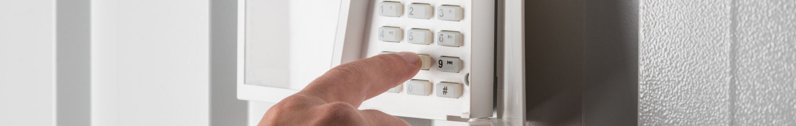 person typing on keypad of security alarm, security system concept